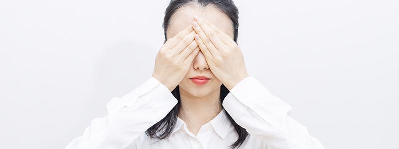 目を両手で塞いでいる女性